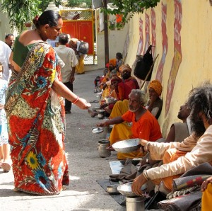 Photograph of woman giving alms to sadhus in Rishikesh, India