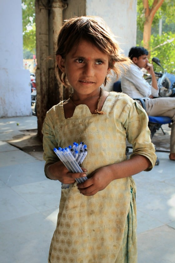 Girl selling pens on the street in Janpath, Delhi, India