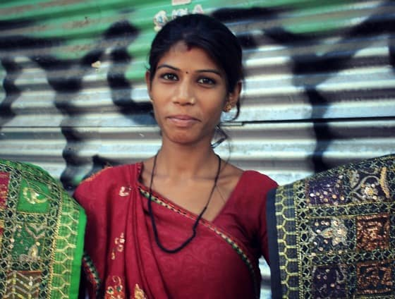 Woman selling tapestries and textiles on the street in Janpath, Delhi, India