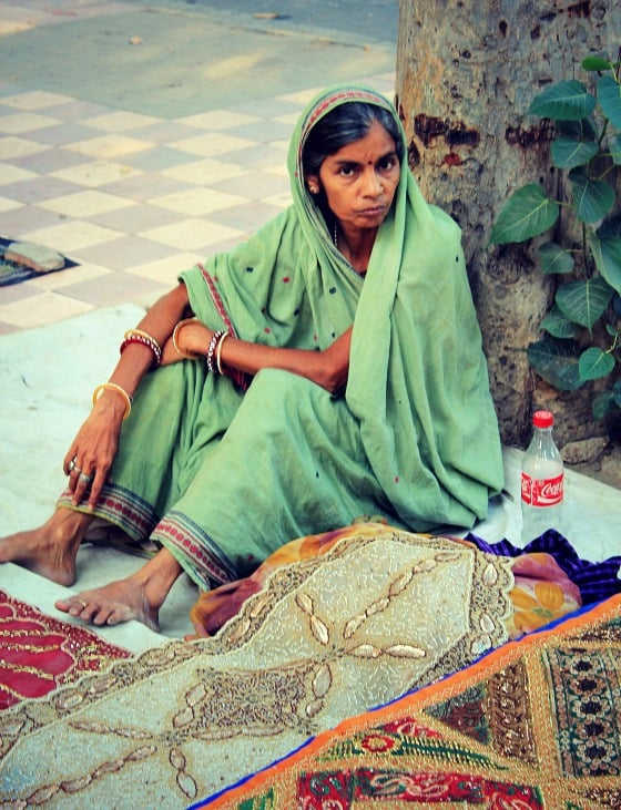 Shopping in India: Woman selling textiles in Janpath street market, Delhi, India