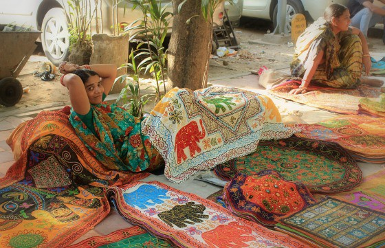 Woman selling tapestries, textiles and wall hangings in Janpath Bazaar, Delhi, India