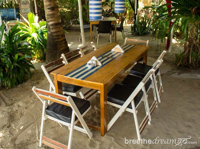 Table with eight chairs on the sand in Goa