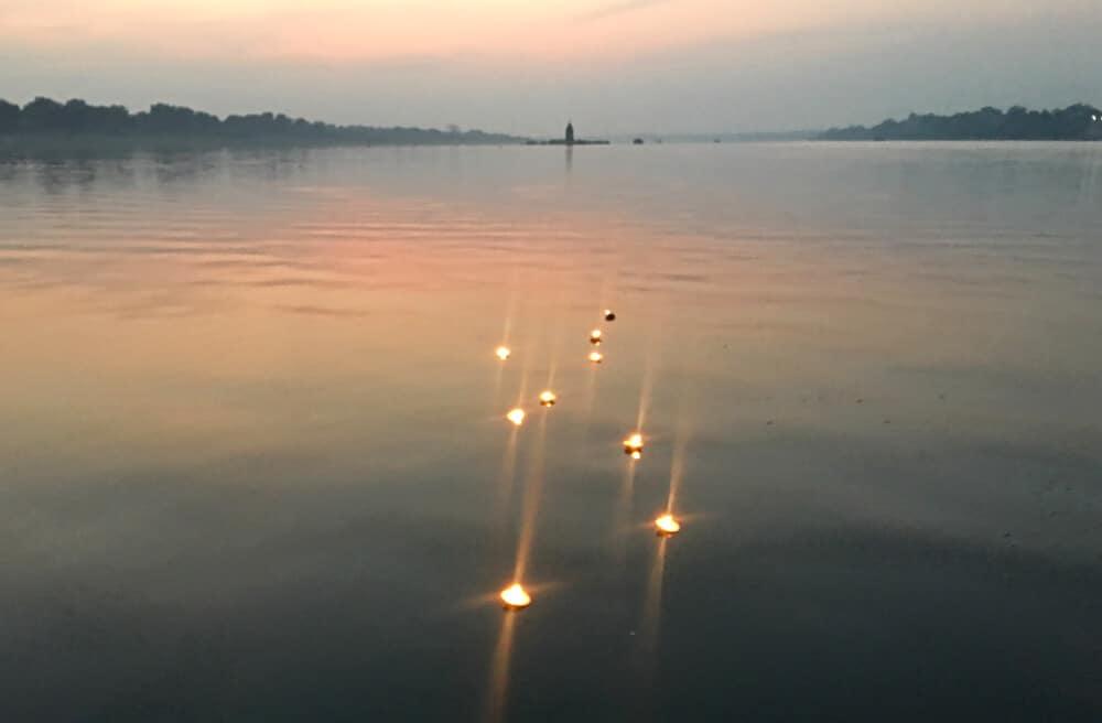 Lght-filled diyas float on the Narmada River in Maheshwar, Madhya Pradesh, India