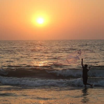 ocean at sunset with man throwing a net