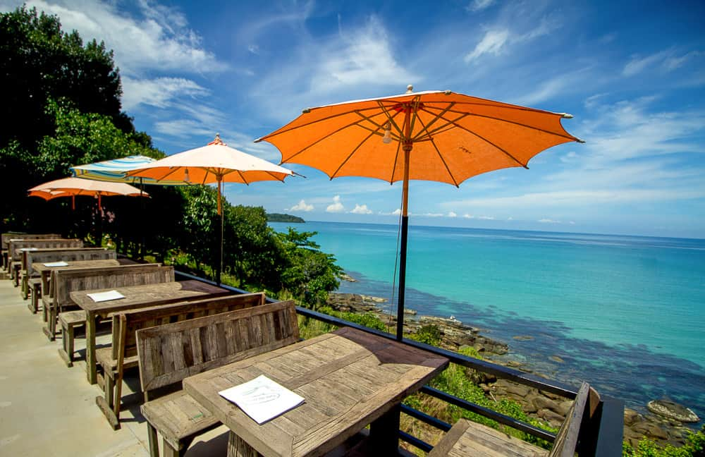 Cafe with orange umbrella overlooking beach in Thailand