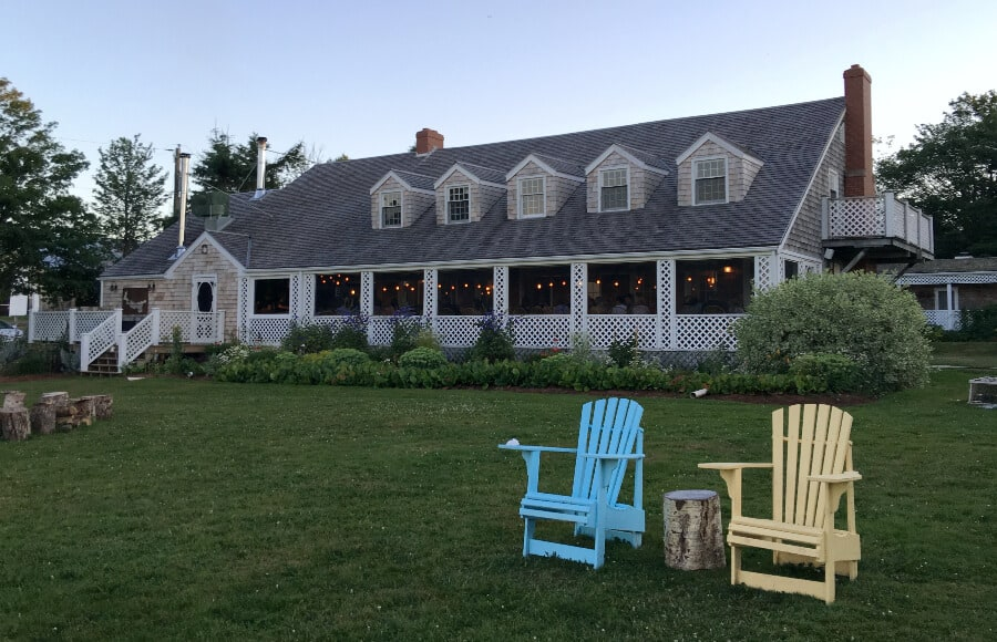 Large wood house with lawn chairs at Inn at Bay Fortune, PEI, Canada