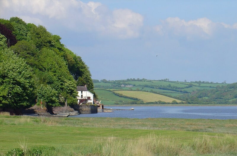 Boat house on a lake with trees, in Laugharne, Wales