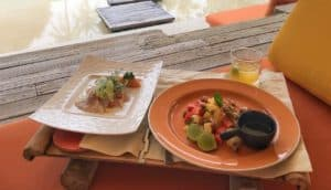 two plates of food and pool at Soneva Kiri, Thailand resort